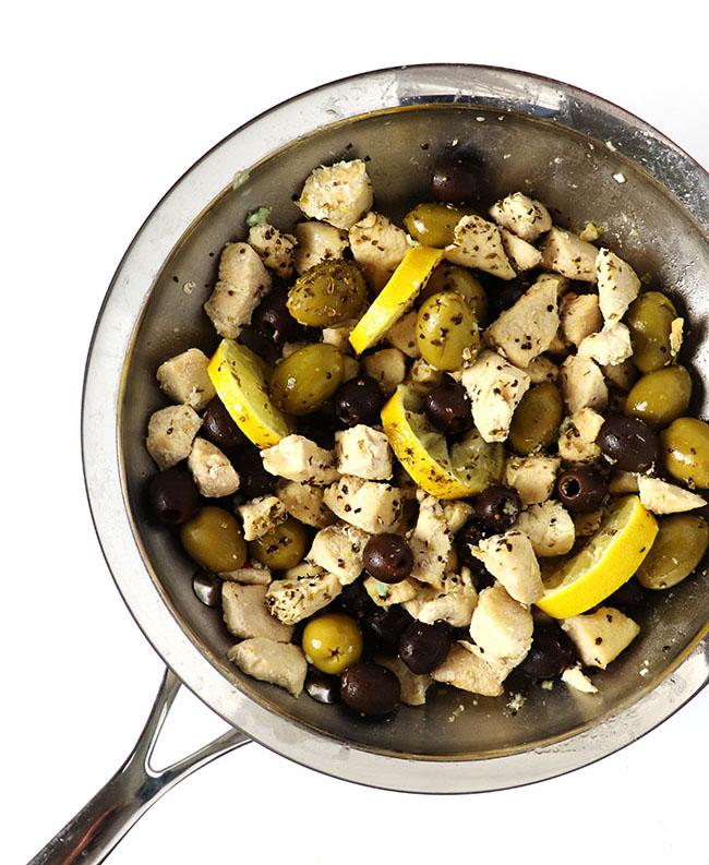 Chicken, olives, and lemon sautéed in a stainless steel skillet for a Mediterranean dish. | spiritedandthensome.com