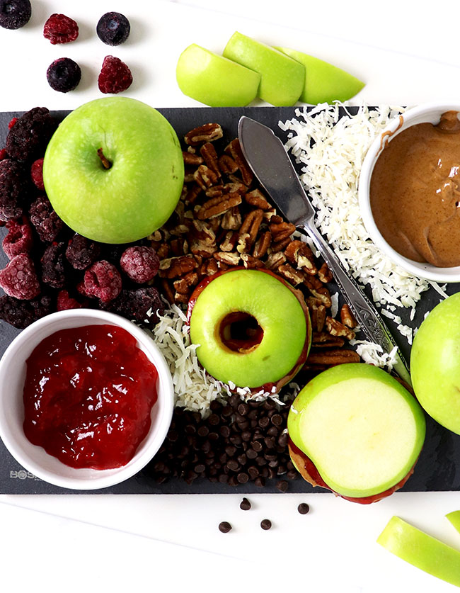 Fruits, mixed nuts, and apples on a slate charcuterie board