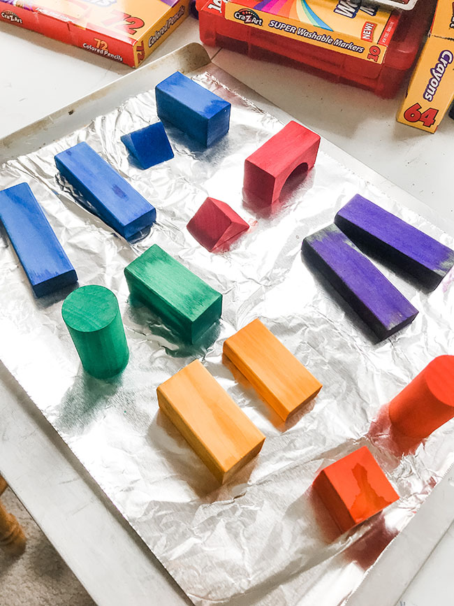 Homemade dyed wooden blocks in blue, yellow, red, green, and orange drying on a piece of aluminum foil