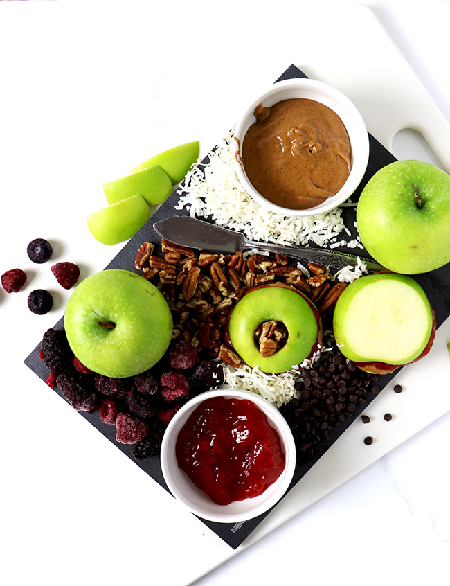 Apple slices, mixed nuts, frozen fruit, and jam on a slate charcuterie board