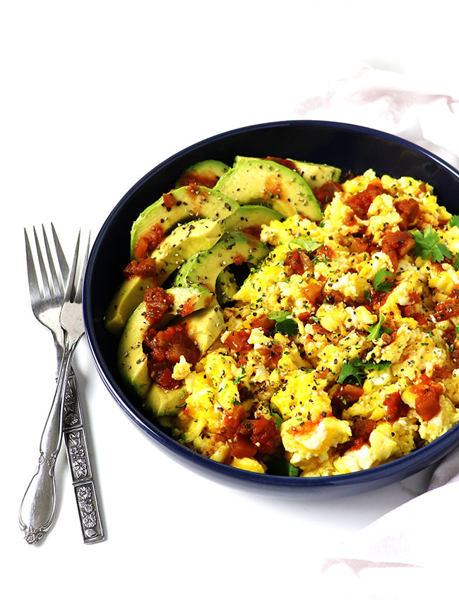 Scrambled eggs, salsa, and avocado in a dark blue porcelain dish
