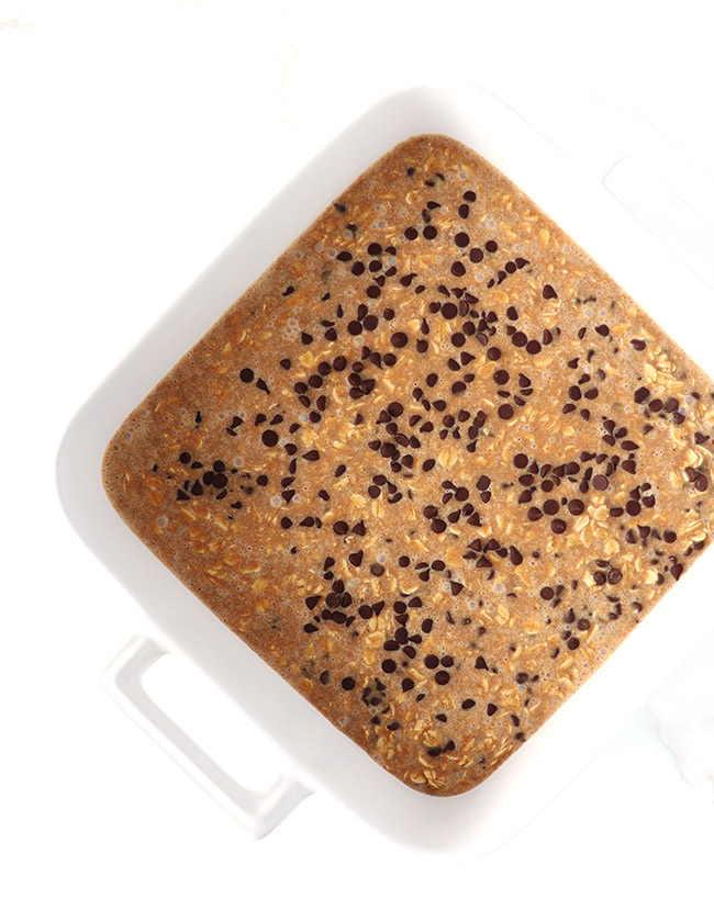 Chilled Chocolate Chip Oatmeal Bars in a white porcelain baking dish on a white marble surface.