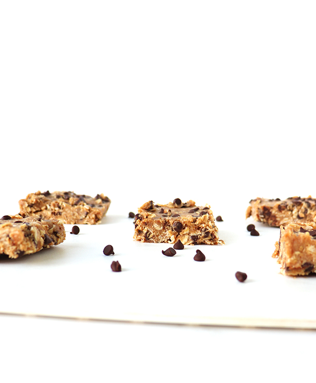 Chocolate Chip Oatmeal Bars on a white cutting and sprinkled with dairy-free chocolate chips