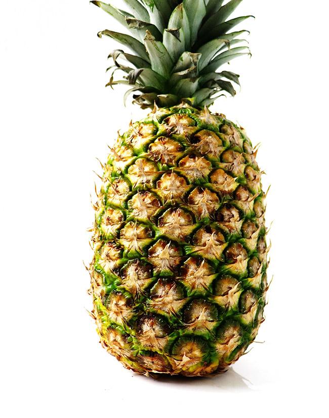 Fresh pineapple on a white marble slab.