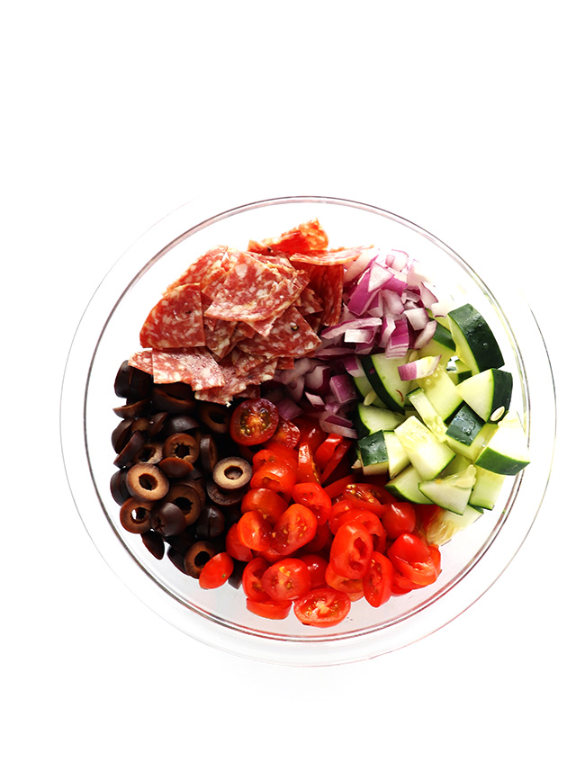 Salami, red onion, black olives, cucumber, and tomatoes in a glass bowl