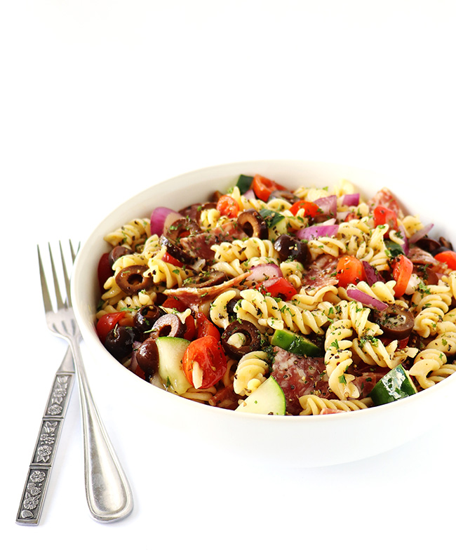 Cooked gluten-free Italian Pasta Salad in a white porcelain bowl with silverware on a white surface