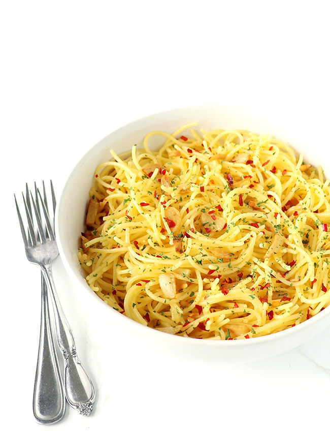 Gluten-free spaghetti in a white porcelain dish on a white marble surface with silverware.