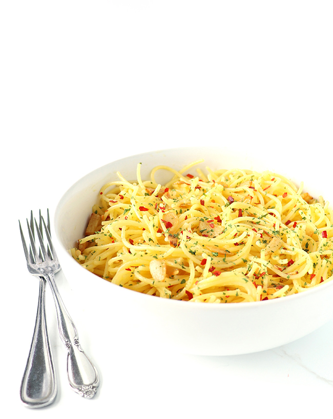 Gluten-free spaghetti in a white porcelain dish on a white marble surface.