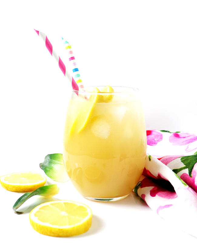 Pineapple lemonade in a clear glass with a floral towel, pink straws, fresh lemons, and pineapple leaves on a marble surface.
