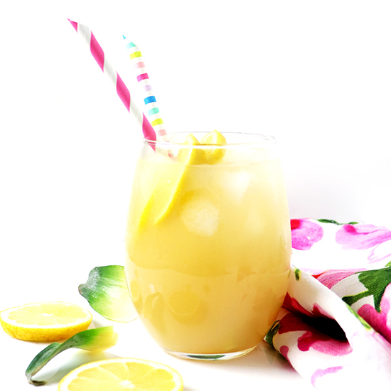 Lemonade in a glass with fresh lemons and pineapple leaves.