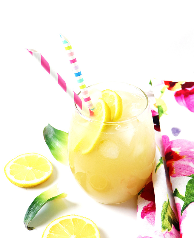 Lemonade in a clear glass with a floral towel, fresh lemons, and pineapple leaves.