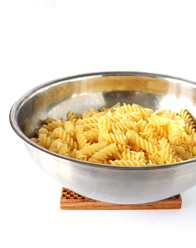 Cooked gluten-free spiral pasta in a stainless steel bowl
