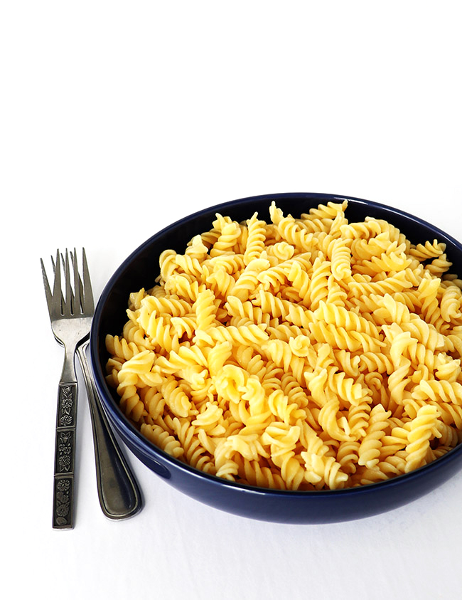 Cooked gluten-free pasta in a blue porcelain dish