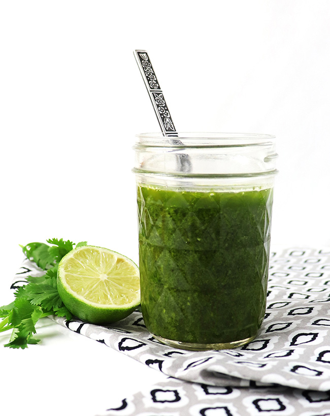 Cilantro Lime Vinaigrette in a glass jar next to fresh cilantro and a fresh lime wedge.