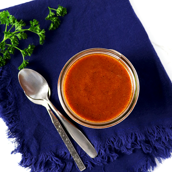 Gluten-Free Enchilada Sauce is a mason jar on top of a royal blue towel.