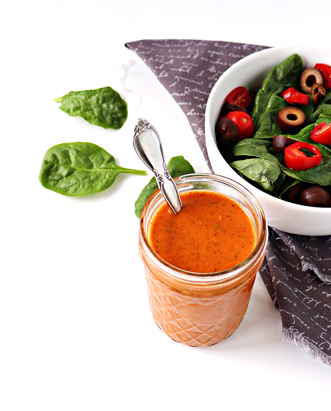 Bright orange salad dressing in a glass jar with a spoon next to a spinach salad on a gray napkin and white marble surface.