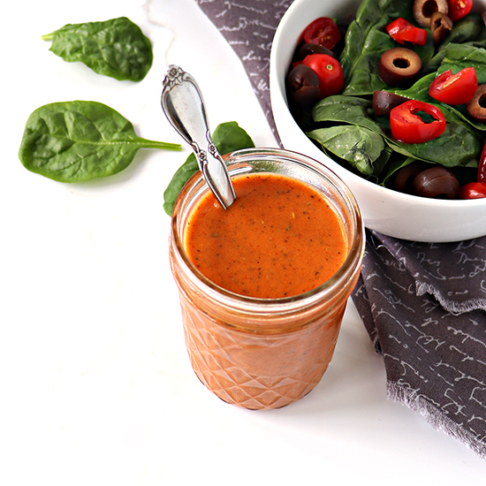Bright orange salad dressing in a glass jar next to a spinach salad on a white marble surface.