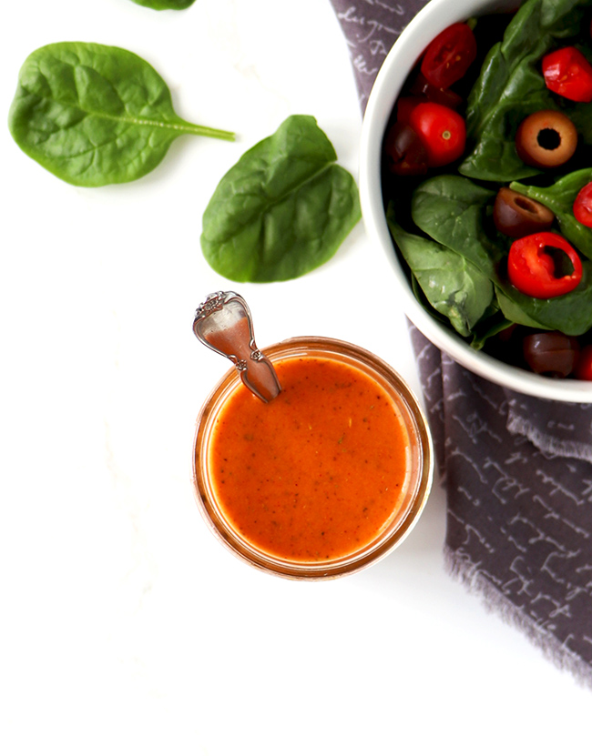 Bright orange Catalina salad dressing in a glass jar next to a spinach salad on a gray napkin and white marble surface.