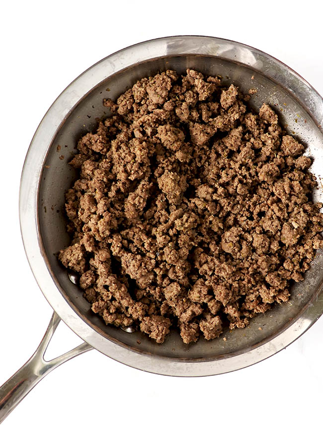 Ground beef cooking in a stainless steel skillet.