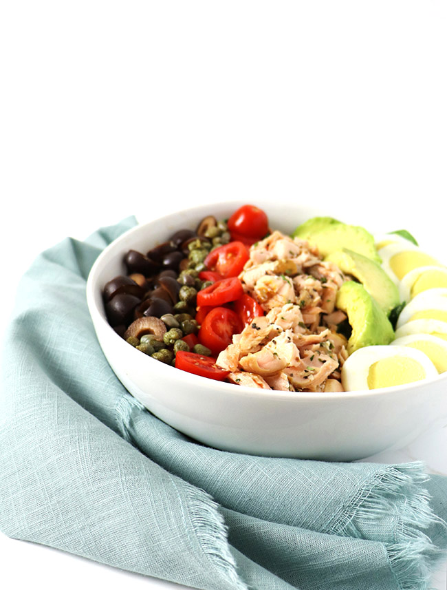 Salmon, black olives, capers, avocado, and eggs in a white dish with a pale green napkin.