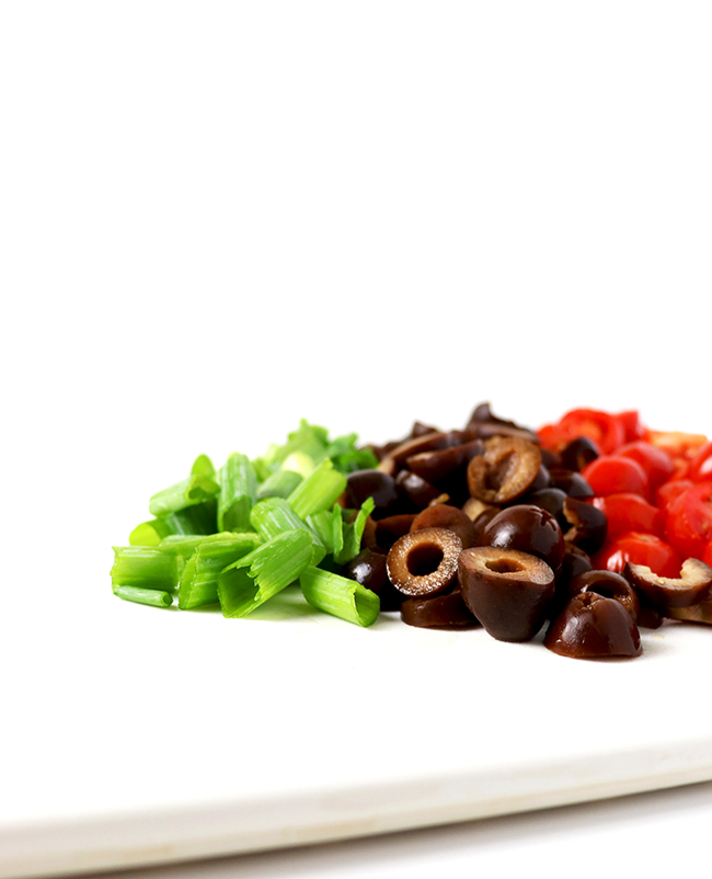 Sliced green onion, black olives, and tomatoes on a white cutting board for Homemade Taco Salad.