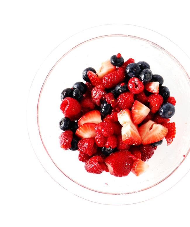 Fresh fruit in a clear glass bowl on a white marble surface in natural light.