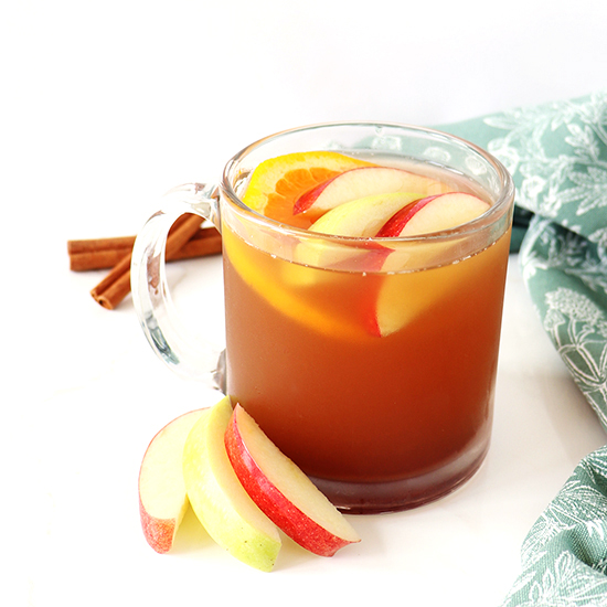 Apple cider in a glass mug with apple slices, orange slices, and cinnamon sticks on a white marble slab.
