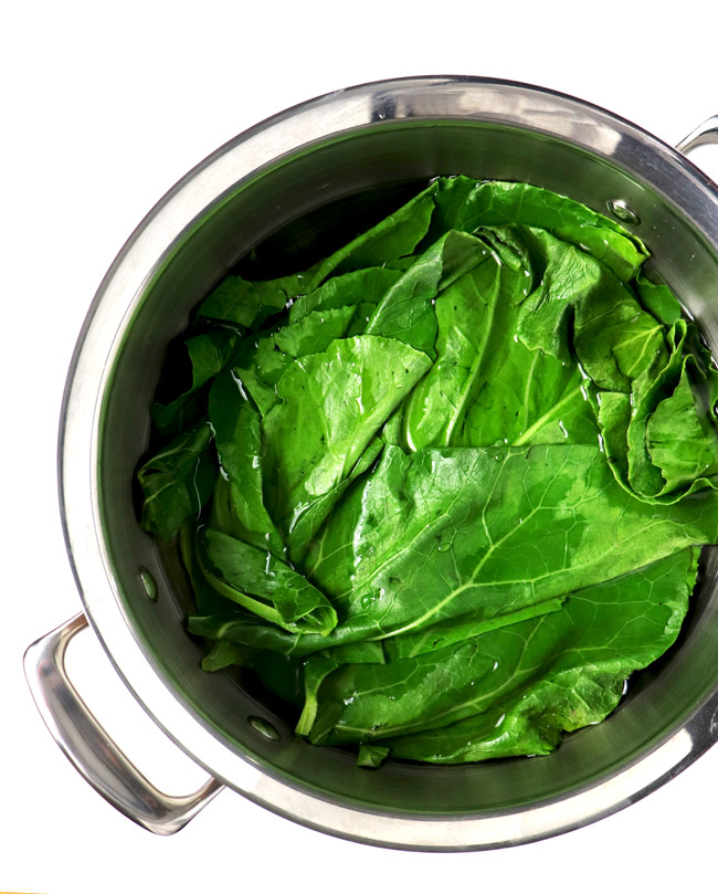 Blanched collard greens in a stainless steel pan of boiling water.