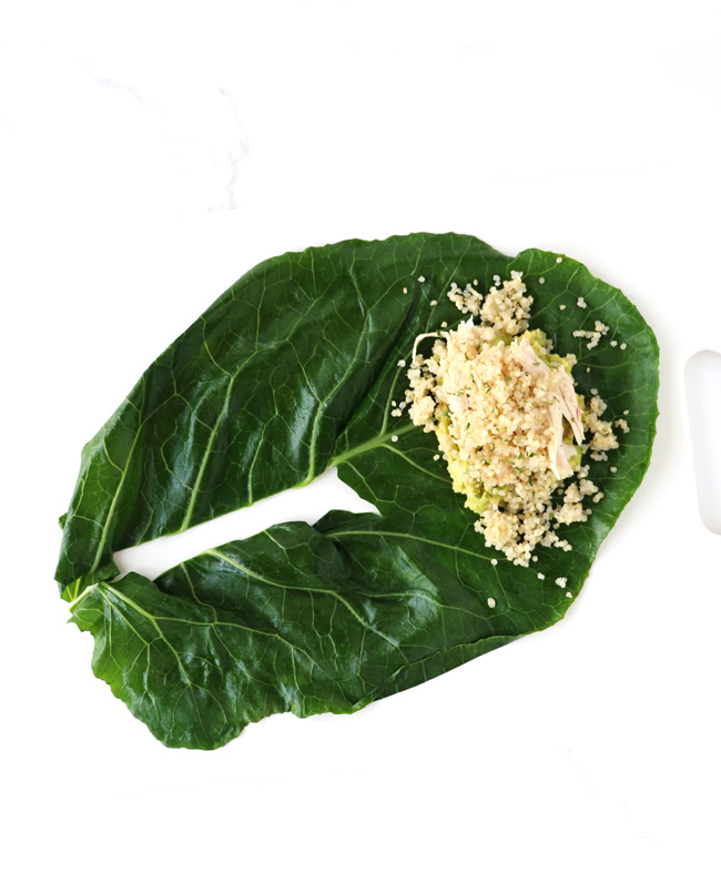 A collard green on a white cutting board with layers of avocado, chicken, and quinoa.