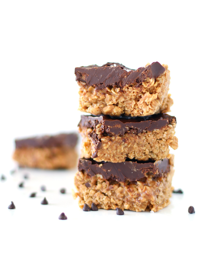 Chocolate Almond Butter Oatmeal Bars stacked on top of each other on a white marble slab with chocolate morsels sprinkled nearby.