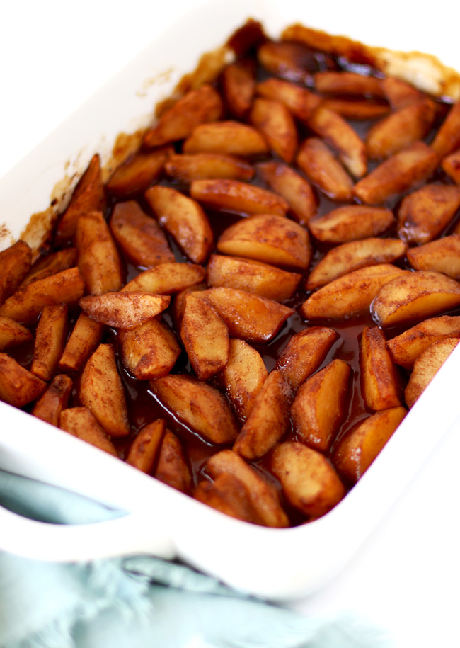 Baked cinnamon apples in a white porcelain baking dish next to a light green cloth napkin.
