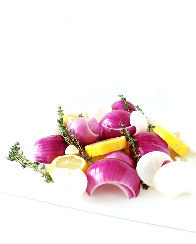 Onions, fresh thyme sprigs, fresh lemons, and fresh garlic on a white cutting board placed on a white marble slab.