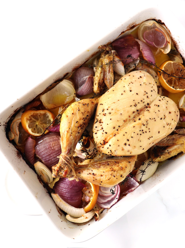 Cooked whole chicken in a white porcelain baking dish, surrounded by lemons, onions, garlic, and sprigs of thyme.