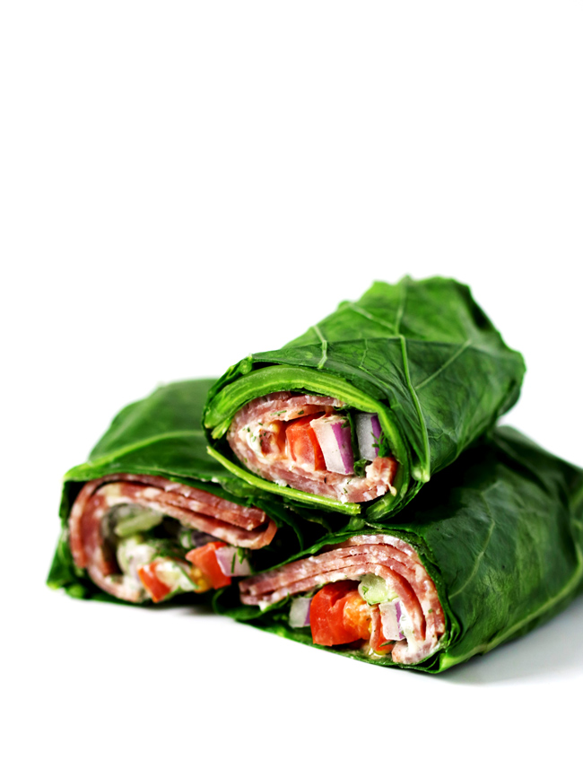 Collard greens wrapped with salami, tzatziki sauce, tomato, and onion on a white marble slab.