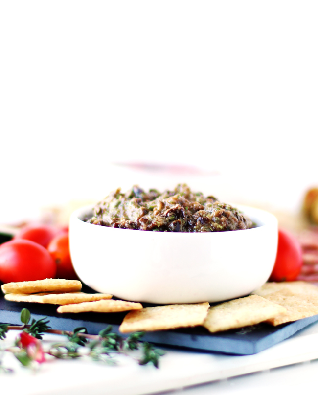 Black Olive Tapenade in a white porcelain dish on a slate charcuterie board with almond flour crackers, sprigs of thyme, pomegranate arils, and grape tomatoes.