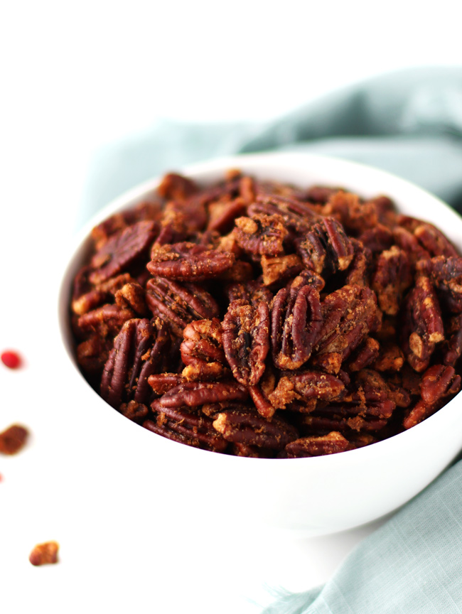 Roasted pecans in a white porcelain bowl with a green napkin and pomegranate arils nearby.