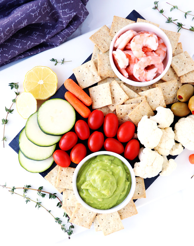 Avocado dip, shrimp, crackers, cauliflower, tomatoes, carrots, and cucumbers on a slate charcuterie board with sprigs of fresh thyme.
