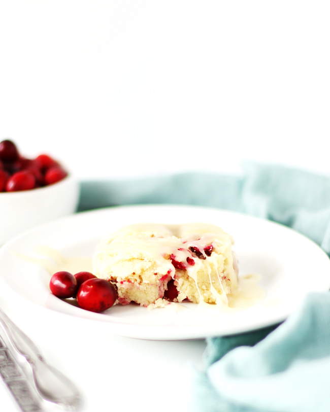 Cranberry cake with butter sauce on a white dish with a green napkin and dish of fresh cranberries behind the plate.