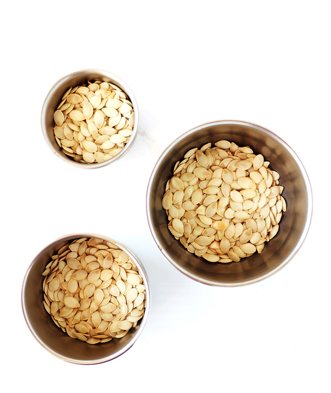 Pumpkin seeds in three stainless steel bowls on a white porcelain surface.