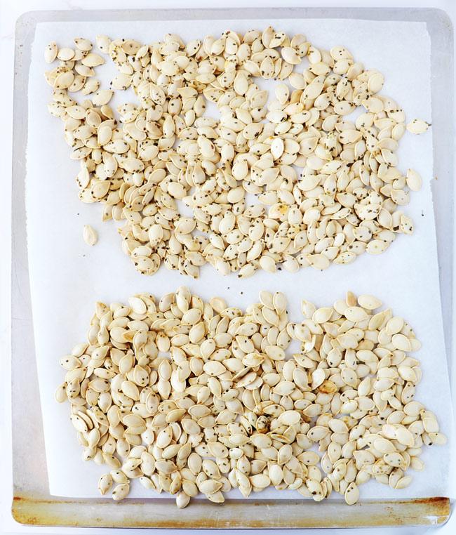 Seasoned pumpkin seeds on a parchment-lined baking sheet.