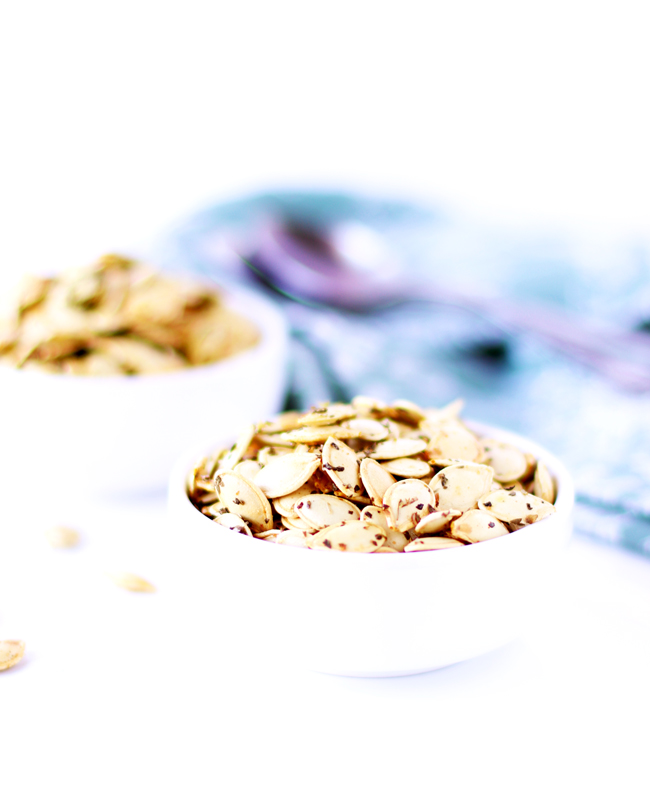 Roasted pumpkin seeds in a white porcelain dish on a white marble slab with a green napkin in the background.
