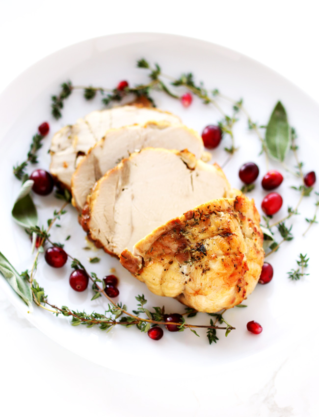 Oven-Roasted Turkey Breast on a white porcelain plate with fresh thyme, sage, and cranberries.