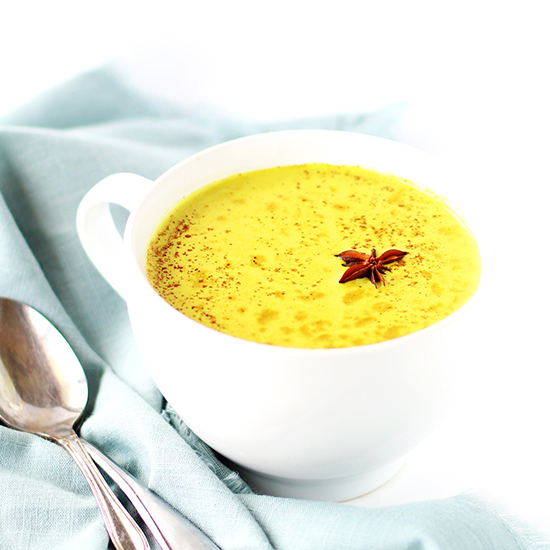 Golden milk in a white porcelain mug on a slab of white marble with a light green napkin and two silver spoons.
