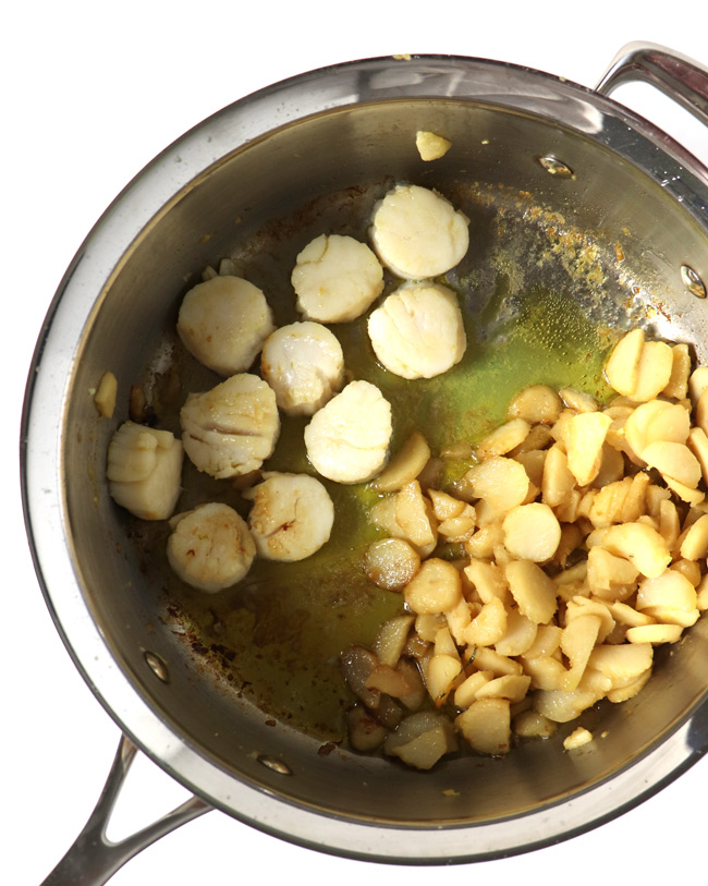 Sea scallops and water chestnuts in a large sauté pan.