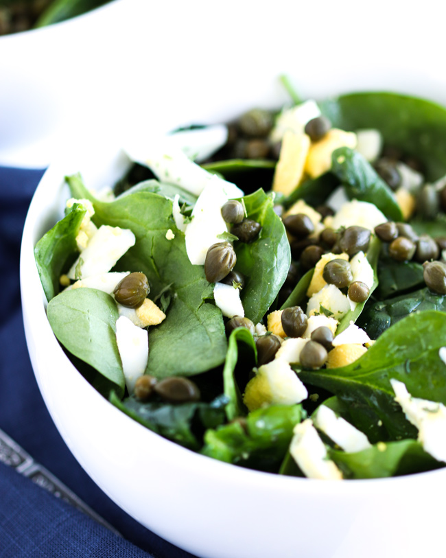 Caper Spinach Salad in a white porcelain bowl next to a blue napkin.