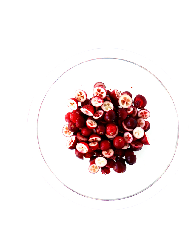 Fresh cranberries in a clear glass bowl.
