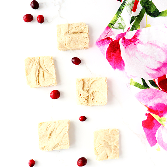 Shortbread bars surrounded by a floral napkin and fresh cranberries, all on top of a white marble surface.
