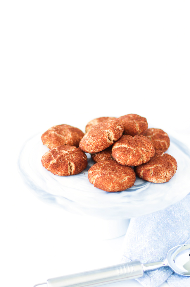 Cinnamon-coated gluten-free snickerdoodle cookies on a white and blue marble cake tray with a light blue napkin off to the side with a silver ice cream scoop.