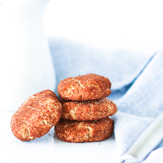 Cinnamon-coated gluten-free snickerdoodle cookies on a white marble slab with a white porcelain pitcher behind it and a light blue napkin off to the side with a silver ice cream scoop.