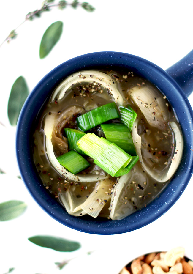 Onions and leeks in a homemade broth in a blue ceramic soup bowl, surrounded by fresh thyme sprigs and sage leaves.